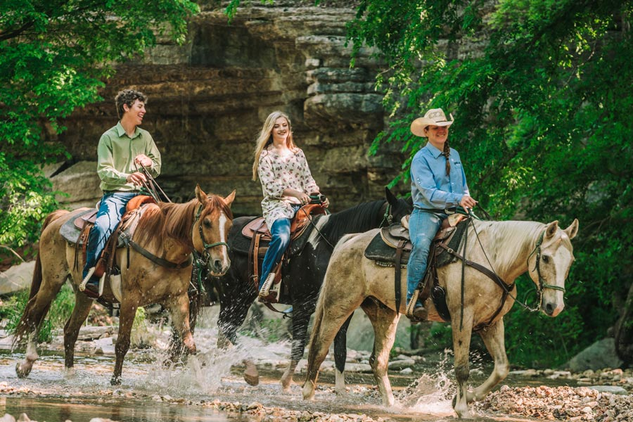 Couple Horseback Riding through Little Indian Creek
