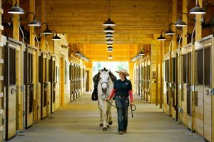 Woman walking horse at Little Indian Stables